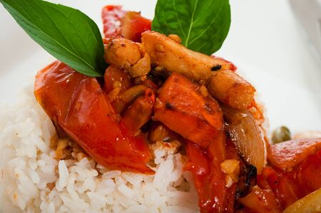 Spicy sliced meat with onions garlic tomato and rice. Some basil leaf as decoration on wood table. photo