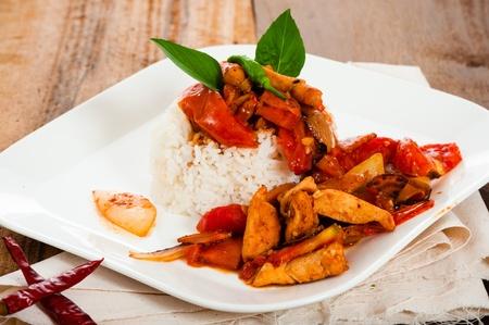 Spicy Aufschnitt mit Zwiebeln Knoblauch Tomaten und Reis. Einige Basilikum als Dekoration auf Holz Tisch. Standard-Bild - 15281458