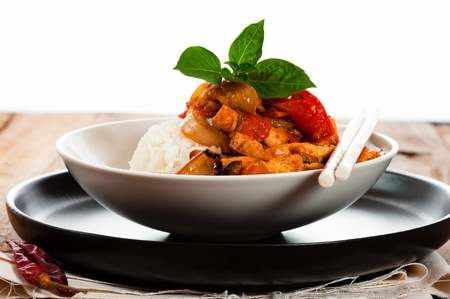 Spicy sliced meat with onions garlic tomato and rice. Some basil leaf as decoration on wood table.