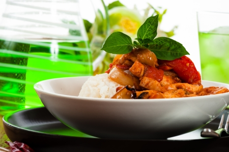 Spicy gesneden vlees met uien knoflook tomaat en rijst. Sommige basilicum blad als decoratie op houten tafel.