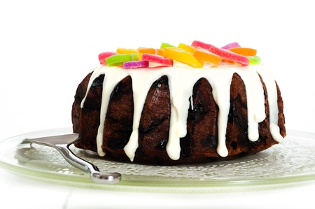 Chocolate cake with white frosting and colorful candies as decoration on white background photo