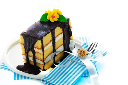 three layered: Small piece of three layer vanilla cake with cream and chocolate  Flower as decoration on the top  White background Stock Photo