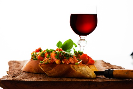 delicious bruschetta appetizer with red wine glass on wooden board Imagens