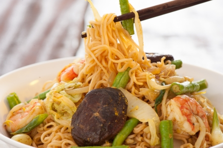 carbonaceous: Spicy asian curry noodles with vegetables shrimps and china mushrooms on wooden table