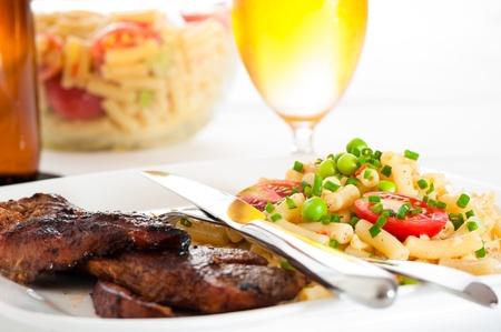 Steak en pasta salade met een glas bier in de achtergrond