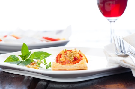 mini pizza: A small piece of mini pizza with some herbs on white plate and a glass of red wine in the background Stock Photo