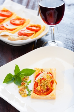 A small piece of mini pizza with some herbs on white plate and a glass of red wine in the background photo