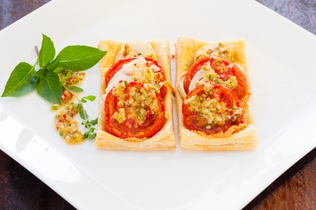 Two small piece of mini pizza with some herbs on white plate photo