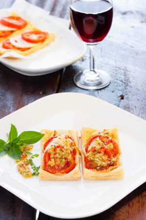 Two small piece of mini pizza with some herbs on white plate and a glass of red wine in the background photo