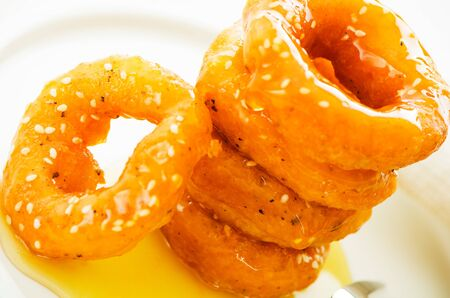 murukku: Mini donuts doing with rice flour soaked with honey on white plate. Typical thai dessert Stock Photo