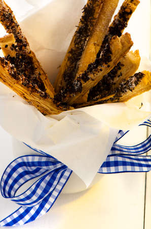 spicy puff pretzel sticks in a white cup with a blue ribbon as decoration on white wooden table photo