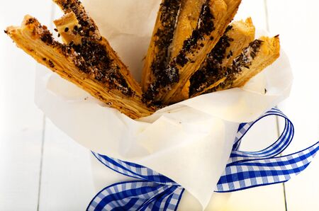 pretzel stick: spicy puff pretzel sticks in a white cup with a blue ribbon as decoration on white wooden table