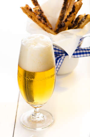 pretzel stick: A glass of beer and spicy puff pretzel sticks in background on white wooden table