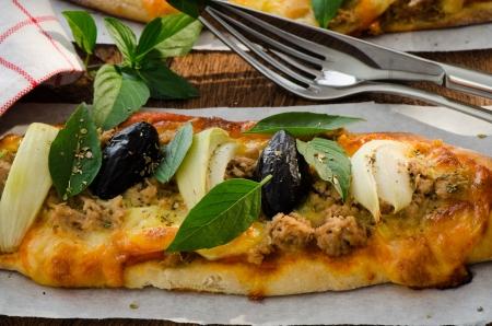 Mini homemade pizza with tuna cheese olive onion and basil on wood plate photo