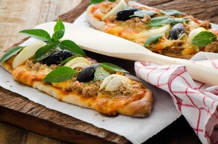 Mini zelfgemaakte pizza met tonijn kaas olijf ui en basilicum op houten plaat