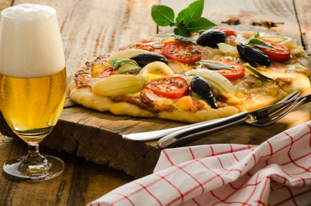 green beer: Homemade bacon pizza with tomatos onion olive basil and a glas of beer on a wood plate Stock Photo