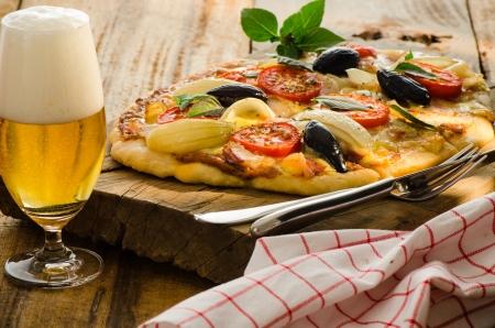 Zelfgemaakte spek pizza met tomaten ui olijf basilicum en een glas bier op een houten plaat