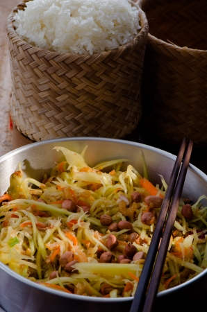 Thai very hot papay salad with a pot of sticky rice on woode table Stock Photo - 17090519