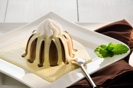 chocolate pudding with vanilla sauce and mint on white plate photo