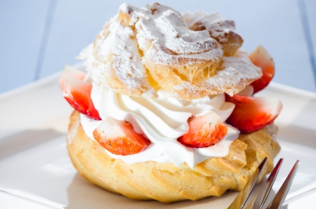 fresh cream puff with whipped cream and strawberries on white plate and light blue wood table