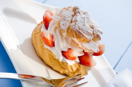 fresh cream puff with whipped cream and strawberries on white plate and light blue wood table photo