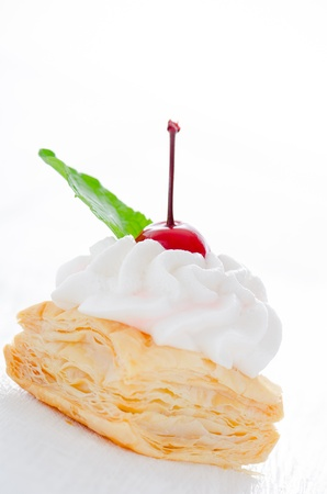 puff pastry cake with cream cherry and fresh mint leaf on white plate photo