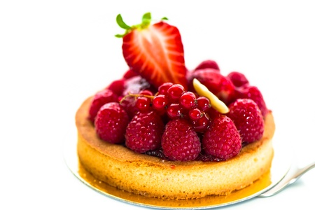 A small fruits tart with strawberry raspberry currant and a piece of chocolate on white background photo