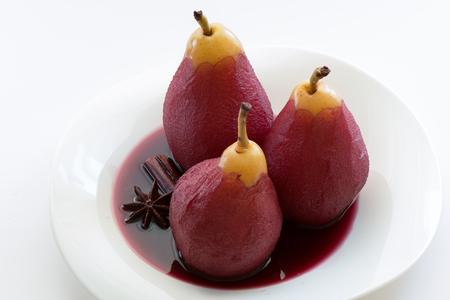 Gepocheerde peren in rode wijn met kaneel en anijs. Witte plaat en een witte achtergrond.