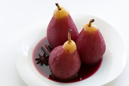 Poached pears in red wine with cinnamon and anise. White plate and white background.
