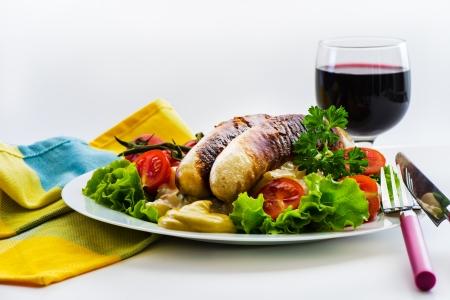 plato de ensalada: Salchichas y plato de ensalada verde con tomates maduros en un plato blanco y un vaso de vino tinto Foto de archivo