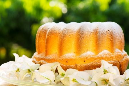 bunt cake op plaat versierd met bloemen en groen
