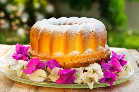bundt cake on plate decorated with flowers and green  Imagens