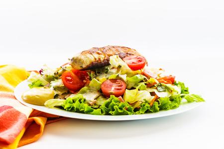 plato de ensalada: Salchichas y plato de ensalada verde con tomate en un plato blanco y un vaso de cerveza Foto de archivo