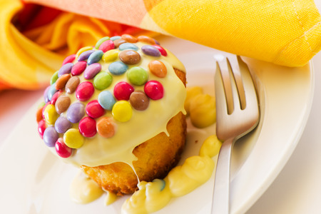 cupcake doused with white chocolate and decorated with smarties photo