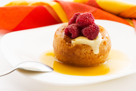 The famous Italian sweet Baba of Naples with rum syrup with fresh raspberry Stock Photo