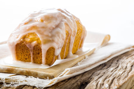 Homemade carrot and almond cake covered in frosting ready to be served on a napkin on old weathered wood, white background photo
