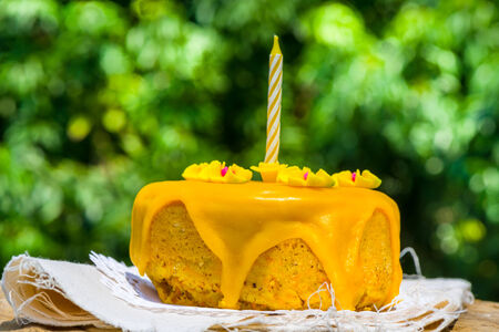Delicious carrot birthday cake topped with orange icing and decorated with flowers with a single central candle on a table outdoors against greenery photo