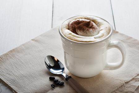 Cup of delicious frothy cappuccino sprinkled with chocolate or cacao powder for an aromatic energising drink