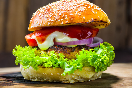 chicken burger: delicious homemade burger with vegetable on wood plate and wood as background Stock Photo