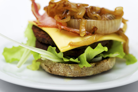 bum: cheeseburger with bacon lettuce, onion tomato and bum on white plate and white background Stock Photo