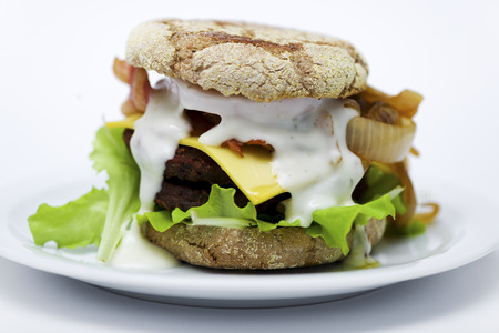 bum: cheeseburger with bacon lettuce, onion tomato bum and bbq sauce on white plate and white background