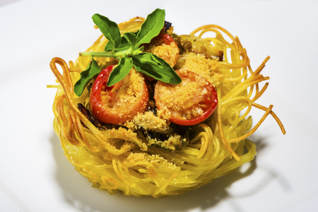 pasta nest arranged on a white porcelain plate with tomatoes parmesan and some leaves of basil Stock Photo