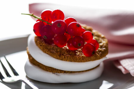 small cake: small cake with cream topping with currant on white plate