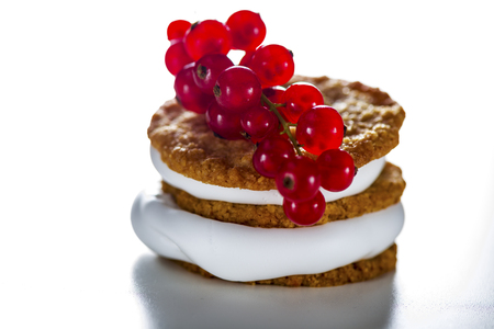 small cake: small cake with cream topping with currant on white background