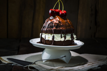 Delicious Chocolate Cake, Served on White Porcelain Tray, with Red Cherries on Top. Place on Top of Napkin at the Wooden Table with Spoon. photo