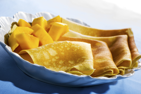 mouth watering: Freshly baked golden pancakes  or crepes neatly folded in a plate and served with fresh diced tropical fruit, close up view