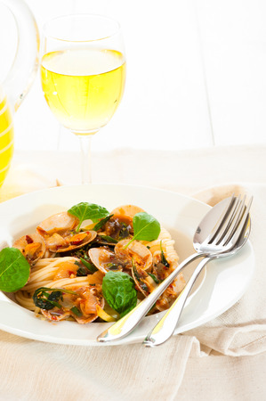 A white plate with delicious spaghetti shellfish and green basil. A glass of white wine in background. photo