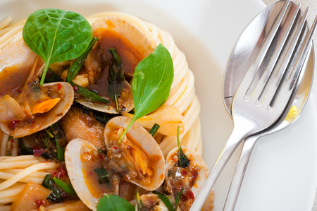 A white plate with delicious spaghetti shellfish and green basil. photo