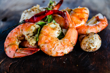 fresh shrimps served on a wood plate with garlic onion and chili