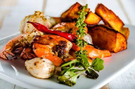camaron: camarones frescos servidos en un plato blanco con cebolla el ajo y chili patatas fritas